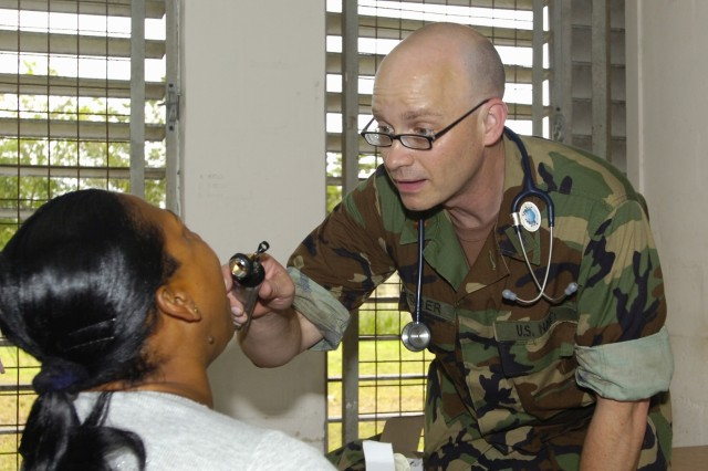 Nurse practitioner Lt. Cmdr. Matthew Ridder, of Operational Health Support Unit (OHSU) - Dallas, conducts basic medical screenings for low-income patients during one of several Beyond The Horizon medical clinics designed to offer free basic medical care. (Photo by Master Sgt. Brenda Benner, Texas Army National Guard)