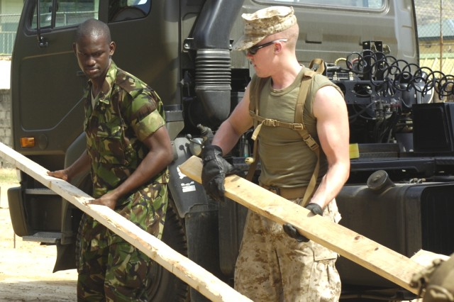 Trinidad and Tobago Defense Force Pvt. Brian Francis, left, and U.S. Marine Corps Lance Cpl. Nathan Arguin of 6th Engineer Support Battalion, 4th Marines Logistic Group, stack lumber for their school construction project during the Beyond the Horizon 2008 multinational exercise.  (Photo by Master Sgt. Brenda Benner, Texas Army National Guard)