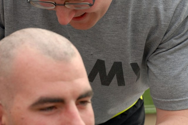 Sgt. James Davy, medic, 566th Area Support Medical Company, grabbed the clippers after shaving his head to aid Spc. Jonathan Strand, medic, 566th Area Support Medical Company in trimming his locks.
