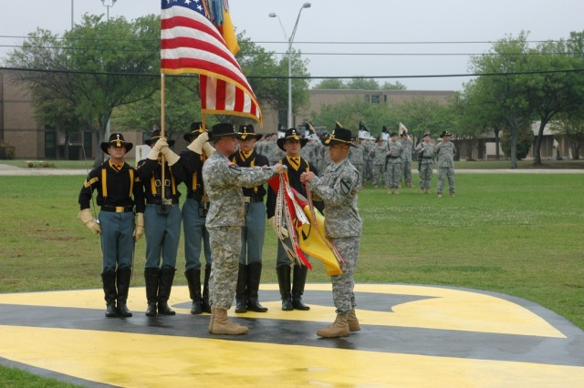 "Col. Dan Shanahan, commander of the 1st Air Cavalry ""Warrior"" Brigade, 1st Cavalry Division, left, and Command Sgt. Maj. Scott Spiva, the brigade's top noncommissioned officer, right, attach a streamer to the brigade guidon during a change of command ceremony April 4 on the division's parade field at Fort Hood, Texas."