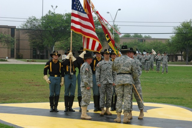 "Col. Dan Shanahan passes the 1st Air Cavalry ""Warrior"" Brigade guidon to Brig. Gen. (P) Vincent Brooks, 1st Cavalry Division commander, as the brigade's top noncommissioned officer, Command Sgt. Maj. Scott Spiva, center, and the incoming commander, Col. Douglas M. Gabram, left, look on April 4 during a change of command ceremony on the division's parade field on Fort Hood, Texas."