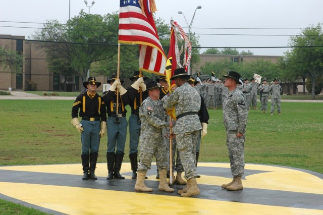 "Brig. Gen. (P)Vincent Brooks, 1st Cavalry Division commander, center, passes the 1st Air Cavalry ""Warrior"" Brigade guidon to it's incoming commander, Col. Douglas M. Gabram, left, as the outgoing commander, Col. Dan Shanahan, right, looks on, during the change of command ceremony on the division's parade field April 4."