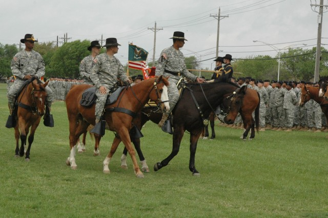 The outgoing commander of 1st Cavalry Division's Division Special Troops Battalion, Lt. Col. Daniel Garcia (center,) leads Brig. Gen. (P) Vincent K. Brooks (right,) the division's commanding general, Lt. Col. Matthew Karres, the incoming commander, and Command Sgt. Maj. Jeffery Moses, the battalion's top noncommissioned officer to review the troops on horseback at a change of command ceremony on Fort Hood, Texas' Cooper Field April 3. Garcia, who hails from East Setauket, N.Y., said that he will miss the division, but knows that his unit will be in good hands, referring to Karres from Chapel Hill, N.C.