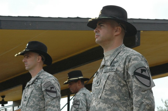 The outgoing commander of 1st Cavalry Division's Division Special Troops Battalion, Lt. Col. Daniel Garcia (right,) stands with his replacement Lt. Col. Matthew Karres while Brig. Gen. (P) Vincent K. Brooks, the division's commanding general, talks about the unit's achievements at the battalion's change of command ceremony on Fort Hood, Texas' Cooper Field April 3. Garcia, who hails from East Setauket, N.Y., said that he will miss the division, but knows that his unit will be in good hands, referring to Karres from Chapel Hill, N.C.