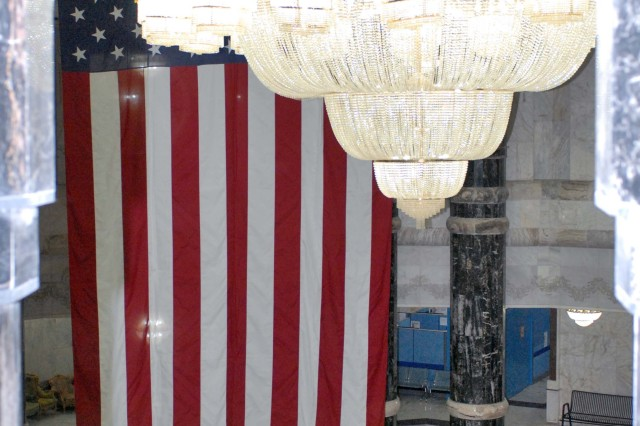 Soldiers raise the garrison flag in the Al Faw Palace rotunda Thursday. The flag was being raised in preparation for a naturalization ceremony Saturday where approximately 200 service members will receive their citizenship. The garrison flag is the largest flag flown by the military, measuring 20 ft. by 38 ft.