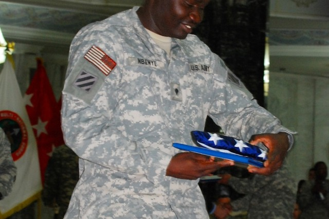 Spc. Simon Nbenye, an Arabic interpreter with Company D, 1st Battalion, 30th Infantry Regiment, 2nd Brigade Combat Team, 3rd Infantry Division, admires his American flag and certificate of naturalization April 12 at Al Faw Palace on Camp Victory during the largest American naturalization ceremony to date in Iraq. Nbenye, a former citizen of Sudan, entered the United States in 2001 under refugee status.