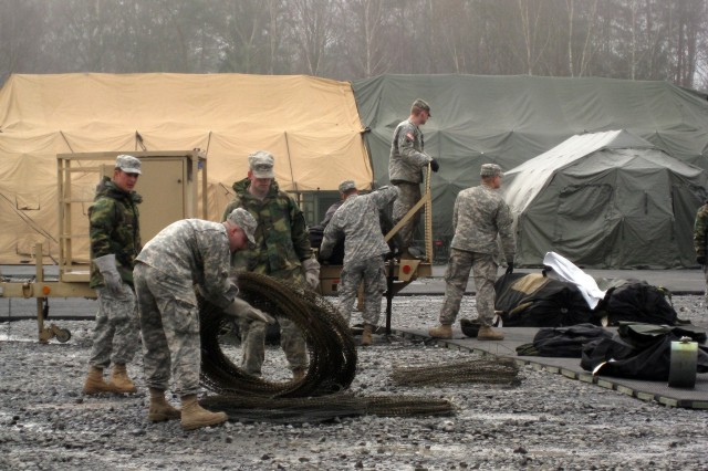 A team of Soldiers works to set up the modular tent structure March 28 to house the deployable command post moved from Heidelberg, Germany to the Grafenwoehr Training Area during the deployment exercise phase of Austere Challenge 08. AC08 a key milestone in the merger of U.S. Army Europe and V Corps into 7th Army.