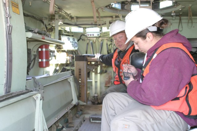 Adam Danes, left, and Crystal Clark work together to identify particular assets of a M113, Armored Personnel Carrier, and input the data on to a PDA type hand held device that will be uploaded to a master storage server in Warren, Mich.