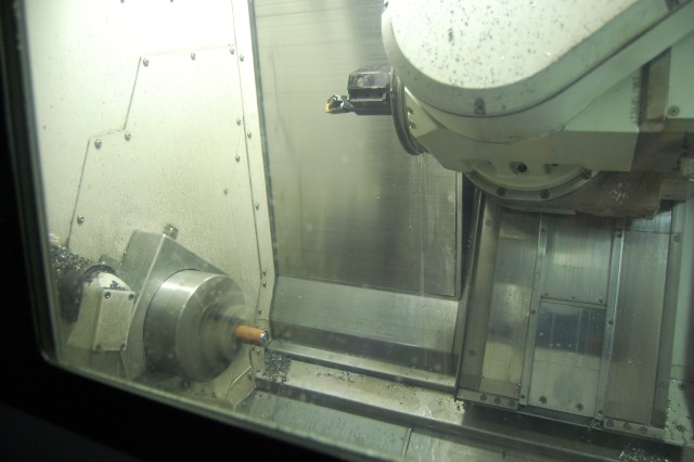 Raw material being transformed into a tool or part is held in place by a rotating 'lathe chuck' (lower left) as the 'head' holding the cutting tool readies to move in.