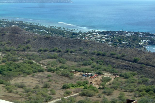 A view from the summit of Diamond Head looking east. In the center is the Fort Ruger environmental restoration project processing site. Immediately beyond the rim is the district of Waialae Kahala (other wise known as the gold coast). In the far background is where Hanauma Bay (a wildlife reserve) is located.