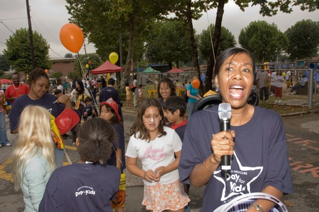 "School Liaison Officer Eskeletha Dorsey (right) makes an announcement at the Yongsan Garrison ""Day for Kids"" event Sept. 15."