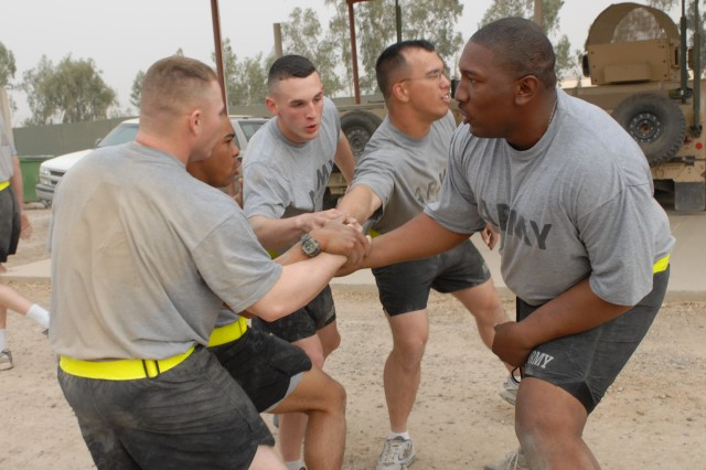 Sgt. Joshua C. Hullum (right), cannon crewman, MNC-I command sergeant major's personal security team, leads his Soldiers in a motivational huddle.
