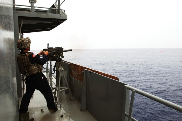 A Soldier aboard the Army Maj. Gen. Charles P. Gross Logistic Support Vessel 5 fires a Browning .50-caliber machine gun at a floating target.
