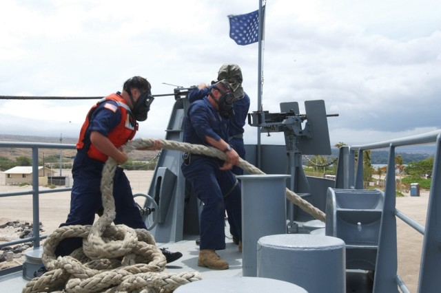 Soldiers aboard U.S. Army Maj. Gen. Charles P. Gross Logistic Support Vessel 5 pull in the lines as the ship makes a hasty retreat from shore during a chemical environment drill.