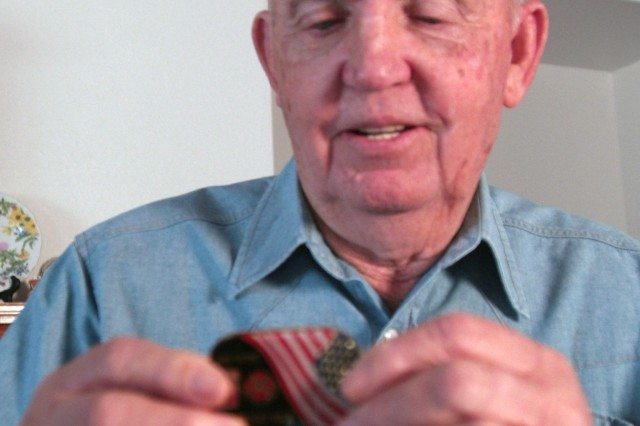 Fred Cryer, 80, holds a commander's coin given to him by Col. David Sage, garrison commander of Fort Polk, La., as part of the installation's efforts to honor people who were forced to move when the Army built the installation. Cryer and his family were displaced twice when Fort Polk was established in the early 1940s. U.S. Army Environmental Command photo by Neal Snyder (neal.snyder@us.army.mil)