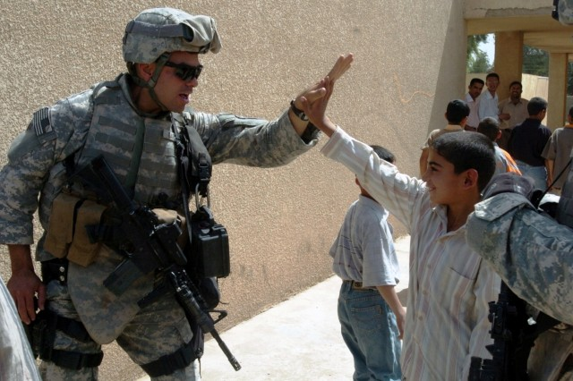 Staff Sgt. Jason Gartsu gets a high-five from a student at Abu Shear School April 14.