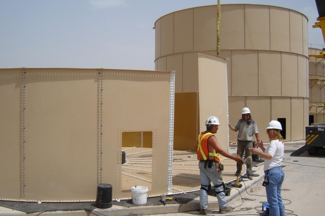 Employees construct a water tank in the theater of operations under the current LOGCAP contract.