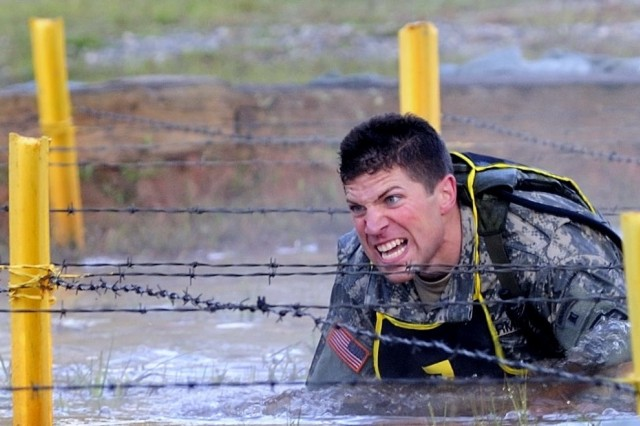 Sgt. Andrew Fuccillo of team 7 representing the 75th Ranger Regiment pushes himself through frigid water and barbed wire in the early morning hours of the 2008 Best Ranger Competition April 18 at Fort Benning, Ga.