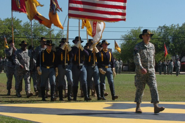 The outgoing top noncommissioned officer of the 1st Cavalry Division Command Sgt. Maj. Philip F. Johndrow of Townsend, Mont., leads the honor guard Soldiers onto the division's black and yellow patch on Cooper Field during a patch ceremony held at Fort Hood, Texas April 18.