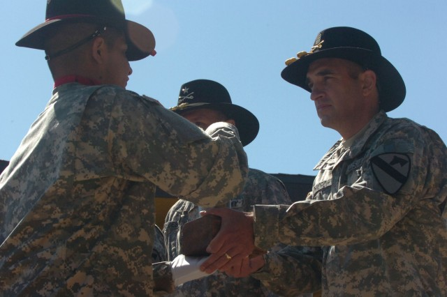 Command Sgt. Maj. Philip F. Johndrow, the outgoing top noncommissioned officer of the division and native of Townsend, Mont., receives the last round fired during a patch ceremony held at Fort Hood, Texas' Cooper Field April 18. The highly-decorated Johndrow enlisted in the Army February 1979.