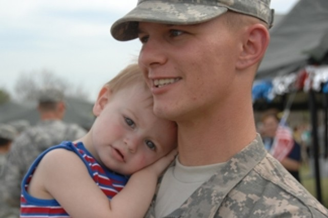 Pfc. Jason L. Pontious, an infantryman with Company A, 1st Battalion, 148th Infantry Battalion, holds son Caleb, during a following the unit's deployment ceremony at Fort Hood, Texas, March 26. A goal for the Army is to ensure one-year deployment times for Guard units such as the 148th, matching them with as many as four to five years at-home time.