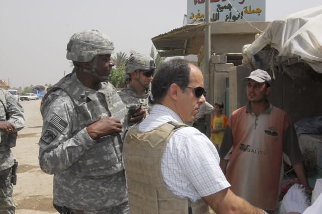 Lt. Gen. Lloyd J. Austin III, commander, Multi-National Corps-Iraq discusses the local economy with a shopkeeper in Hawr rajab.
