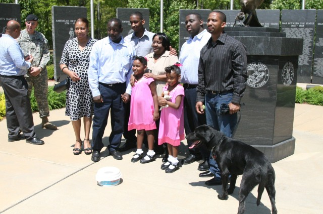 Bo, a newly-retired specialized search dog, poses with his new Family Friday in Lawrenceville, Ga.
