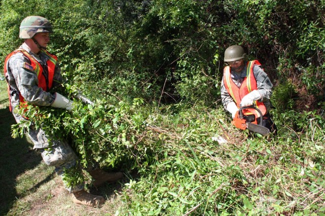 Two Soldiers from Detachment 1 of the 1221st Engineer Battalion (Route Clearance), a South Carolina National Guard unit from Batesburg, clear debris from a creek that during a training scenario has overflowed the banks in a Beaufort County community during the Vigilant Guard 2008 exercise.
