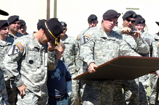 Soldiers of Dagger Troop, 1st Battalion, 82nd Field Artillery, 1st Brigade Combat Team, 1st Cavalry Division present Alma, Mich., native 1st Sgt. Richard Fisk, the top noncommissioned officer of Dagger Troop with a framed Dagger guidon engraved with a reflection of their motto after their deactivation ceremony on Fort Hood, Texas April 15.