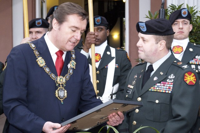 Hanau Lord Mayor Claus Kaminsky, left, reads a commemorative plaque before presenting it to Col. Ray Graham, commander of U.S. Army Garrison Wiesbaden, during a special farewell ceremony at Hanau's Olof-Palme Haus April 17.
