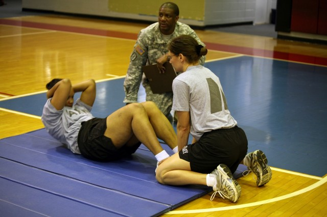 Col. Cheryl Lewis completes the sit-up portion of the PT test as Maj. Pamela Tingle assists by holding her feet and Sgt. 1st Class Willie Kelly counts.