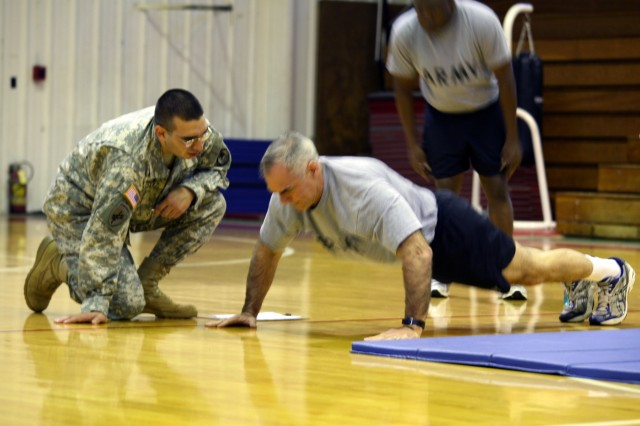 Col. John C. Hamilton, SMDC/ARSTRAT chief of staff, performs push-ups as Staff Sgt. Marcus Church counts.