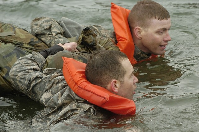 Specialist Brian Martin, left, and Pfc. Dustin Summerville, from C Trp., 1-14 Cav. swim with their poncho raft in Fort Lewis' Sequalitchew Lake.