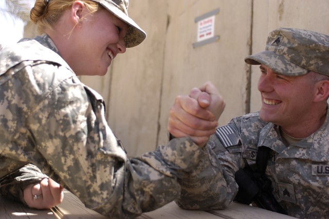 Pfc. Elizabeth A. Stuart, evaluations clerk with the Task Force Dragon personnel shop, takes a hand in arm-wrestling her husband, Sgt. Beau G. Stuart, assistant convoy commander for 2nd Section, Headquarters Support Company, Task Force Dragon.
