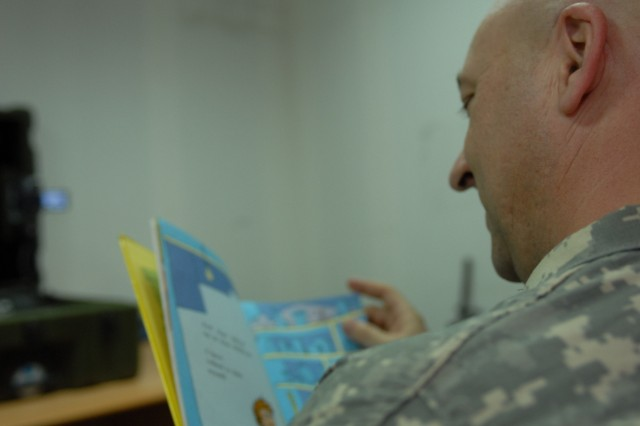 Maj. Mike Kepner, battalion executive officer, Task Force Dragon, reads a Dr. Seuss book to his five-month-old son at the MNC-I Chaplain's Office Saturday.  Kepner reads for his son back home in Southern Pines, N.C., once a week.