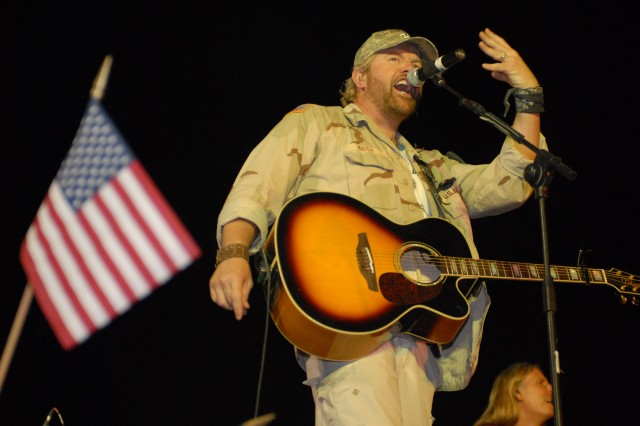 "Toby Keith performs for servicemembers at the Liberty Post Exchange, Camp Liberty, Iraq April 26.  This is Keith's sixth United Services Organizations tour and he will be visiting locations throughout Afghanistan and Iraq.  ""I just want [the troops] to have a good time, and I want to know when we leave that we brought some sense of home to them, and for a little while maybe it'll lighten their world up and they'll remember what they're fighting for,"" Keith said."