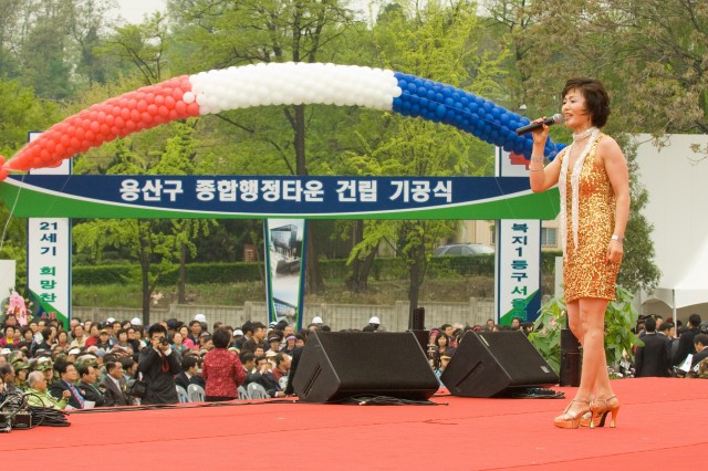 A Korean singer entertains the 5,000-plus crowd April 25 at the Yongsan Ward Adminstrative Complex ground-breaking ceremony. Yongsan Garrison is visible across the road from the construction site.