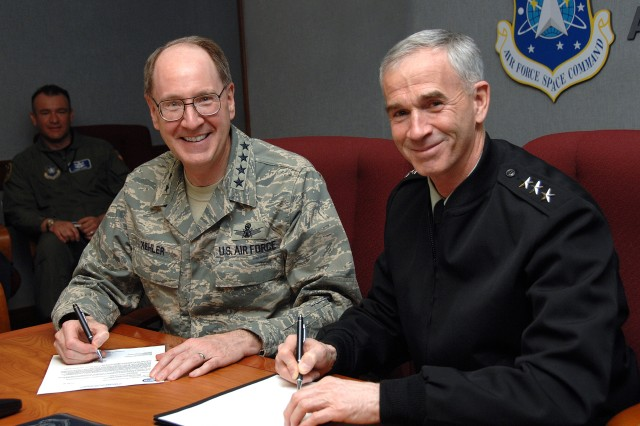 Air Force Gen. C. Robert Kehler, commander, Air Force Space Command; and Army Lt. Gen. Kevin T. Campbell, commander of the Army Space and Missile Defense Command/Army Forces Strategic Command at Redstone Arsenal, Ala., sign a memorandum on April 11 at Peterson Air Force Base, Colo., recommending early USSTRATCOM acceptance of command and control of the first Wideband Global SATCOM satellite.