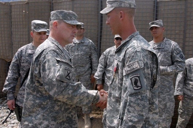 Army Brig. Gen. Mark Milley, CJTF-101 deputy commanding general of operations, presented a coin for excellence to Sgt. Ryan P. Inabnet, 173rd Airborne Brigade Combat Team, 1-91 Cavalry Squadron, after awarding him the Bronze Star for valor, April 24, at Fire Base Naray, Kunar province. Inabnet was recognized for saving more than a dozen Soldier's lives while acting with a Quick Reaction Team re-enforcing International Security Assistance Forces battling insurgents. He provided first aid to several wounded Soldiers and transported numerous casualties to a medevac point.
