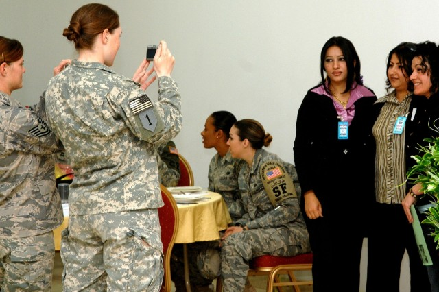A Soldier and Airman take pictures at the first Northern Iraq Women's Conference held in Kirkuk, Iraq, April 20. First of its kind in the region, the conference brought close to 100 female Iraqis throughout the Kirkuk Province and U.S. professionals to include female Peshmerga Soldiers from Sulayminiyah, and U.S. Army and Air Force personnel stationed at FOB Warrior together.