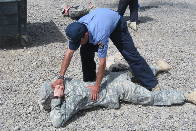 Iraqi Police officers from the Tahrir IP Station in Iraq demonstrate proper personnel searches during training with Soldiers 4th Brigade Combat Team, 3rd Inf. Div., April 23 at Forward Operating Base Iskan, Iraq. Pvt. Jeffery Morris and Pfc. James Vanderheyden are the two Soldiers on the ground being searched.