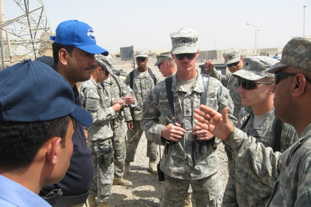 Staff Sgt. Jon Kraft and Sgt. Adam Smith, both with 4th BCT, 3rd Inf. Div., speak with an IP officer from the Tahrir Iraqi Police Station in Iraq during training April 23 at FOB Iskan, Iraq.