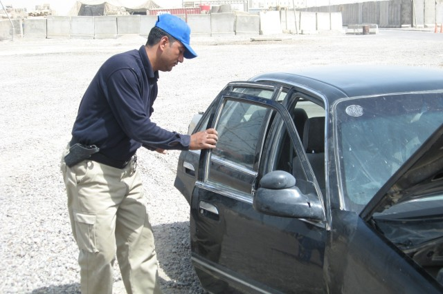 An IP officer from the Tahrir Iraqi Police Station in Iraq searches a vehicle during training with Soldiers from 4th BCT, 3rd Inf. Div., April 23 at FOB Iskan, Iraq.
