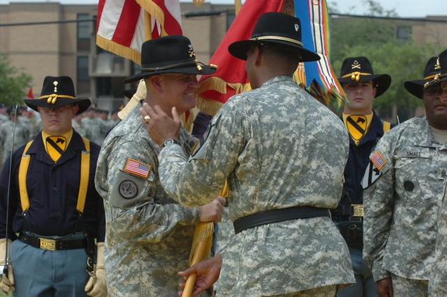 """After handing the 1st """"Ironhorse"""" Brigade, 1st Cavalry Division guidon to Col. Tobin L. Green, incoming commander, Brig. Gen. (P) Vincent K. Brooks, the commanding general of the division, gives Green, who has just accepted command of the Ironhorse Brigade, a pat on the shoulder during a change of command ceremony April 25 at Fort Hood, Texas. """""""