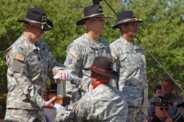 The new commanding general of the 1st Cavalry Division Maj. Gen. Daniel P. Bolger (left) of Aurora, Ill., receives the first round fired from a First Team Soldier during the his change of command ceremony held at Fort Hood, Texas', Cooper Field April 29. Alexandria, Va., native Brig. Gen. Vincent K. Brooks (right), the outgoing division commander, will be staying at Fort Hood, but moving to the U.S. Army's III Corps.