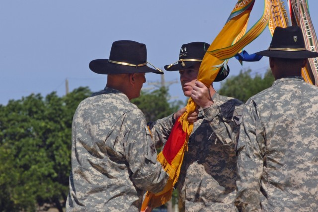 The new commanding general of the 1st Cavalry Division Maj. Gen. Daniel P. Bolger (center) of Aurora, Ill., accepts the First Team's colors of the from Lt. Gen. Raymond T. Odierno, the commanding general of III Corps who grew up in northern New Jersey, during the unit's change of command ceremony held at Cooper Field at Fort Hood, Texas, April 29.
