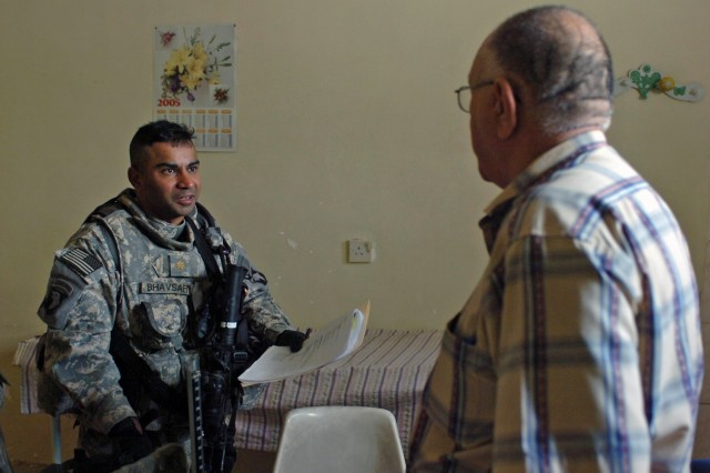 Maj. Amit Bhavsartalks with a doctor while at a health clinic in western Baghdad community of Iskan April 27. Bhavsar serves as the brigade surgeon for the 2nd Brigade Combat Team, 101st Airborne Division (Air Assault), Multi-National Division - Baghdad. He visited three hospitals in western Baghdad to see their equipment shortfalls.