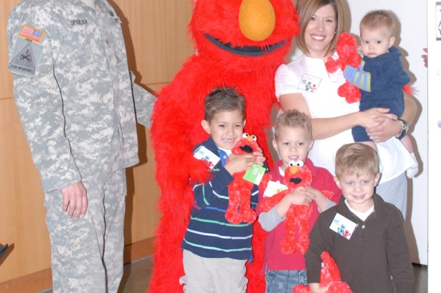 "Maj. Greg Spencer, Elmo, his sons Sam, 6, Ethan, 5, his wife Heather, Gabe, 3, and Joel, 9 months, pose April 29 before the launch of the new Sesame Workshop DVDs for military children, ""Talk, Listen, Connect: Deployments, Homecomings, Changes."""