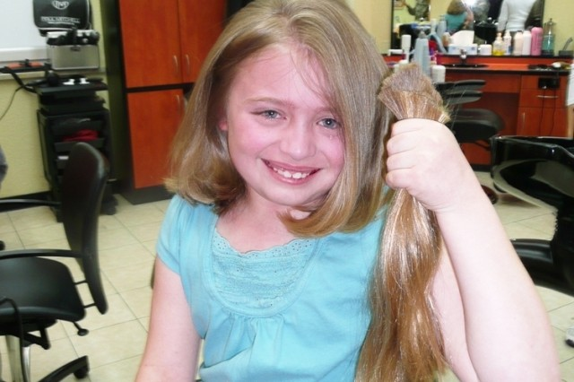 Carolyn Bradley, 9, holds up a foot of hair of hair she donated to Locks of Love, an organization that provides hairpieces to children suffering from long-term medical hair loss.