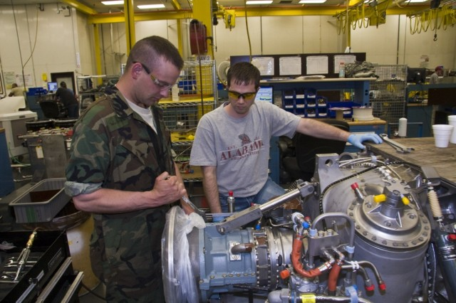 Members of the North Dakota Army National Guard completed hands-on training in the depot's engine repair shops this week. Here, Spc. Brian Wollmuth works alongside depot mechanic Jonathan Hathaway.